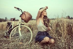 Ung kvinde i udkanten af en mark med sin cykel og cykelkurv