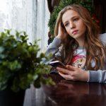 ung-kvinde-sidder-ved-et-bord-med-sin-mobiltelefon-og-keder-sig-kedsomhed